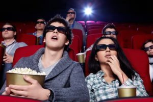 Surprised people in 3D glasses in cinema